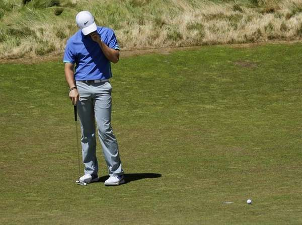 Rory McIlroy, of Northern Ireland, reacts after missing