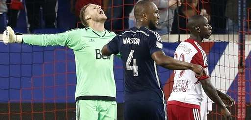 Vancouver Whitecaps FC goalkeeper David Ousted, right, celebrates