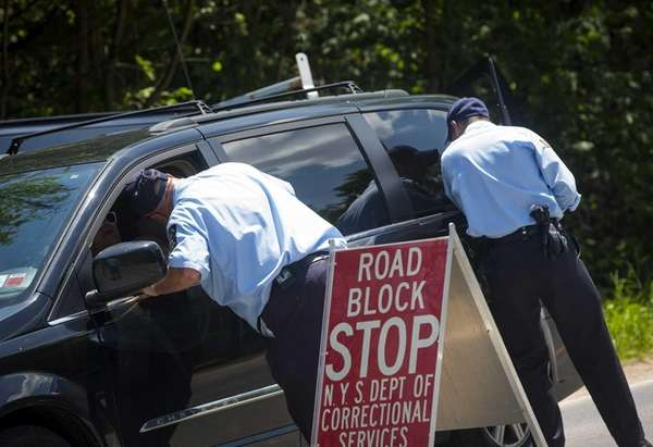 Department of Corrections officers work a roadblock in