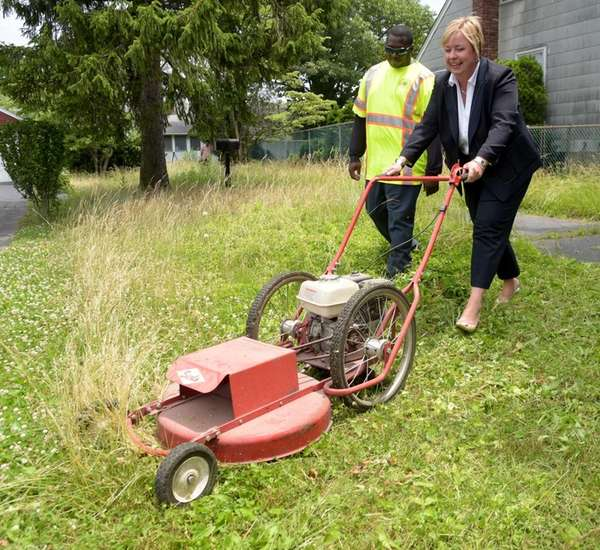 Town of Hempstead Supervisor Kate Murray mows the