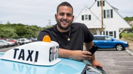 Mark Ripolone, owner of Ditch Plains Taxi, stands