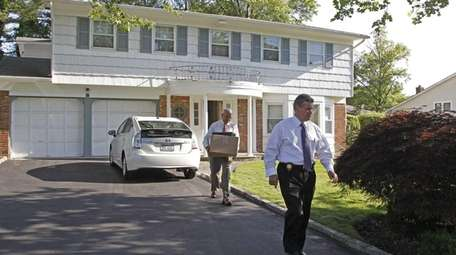 Nassau County homicide detectives carry out evidence on