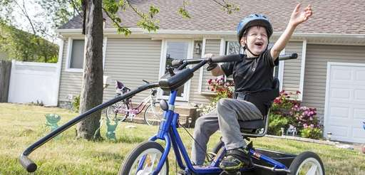 John Graham, 8, on his adaptive tricycle in