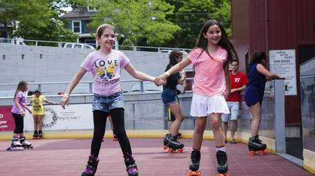 Ashlyn Evans, 9, of Farmingville, holds hands with
