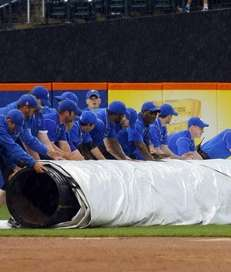The grounds crew bring out the tarp after