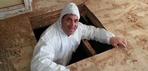 Andrew Braum inspects the crawlspace of a home