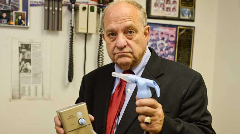 Islip asthma specialist Dr. Harvey Miller stands with