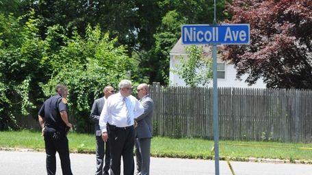 Suffolk County police investigators gather on Nicoll Avenue