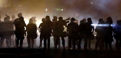 Police walk through a cloud of smoke as