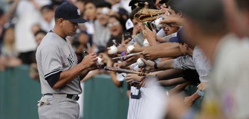 New York Yankees' Alex Rodriguez signs his autographs