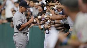 New York Yankees' Alex Rodriguez signs his autographs