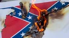 Protesters burn a paper Confederate flag during a