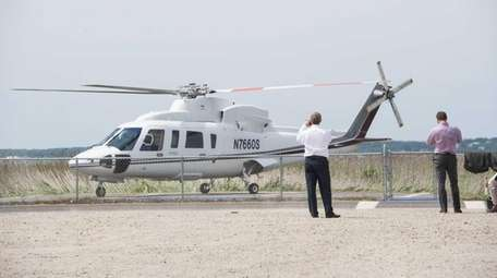 Passengers wait to board a helicopter landing at