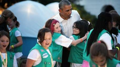 President Barack Obama hugs Girl Scouts who traveled
