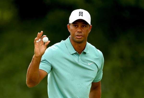 Tiger Woods waves to the gallery after making