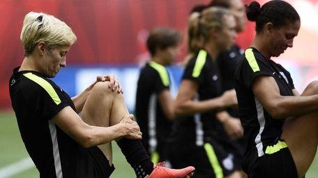 USA midfielder Megan Rapinoe (L) takes part in