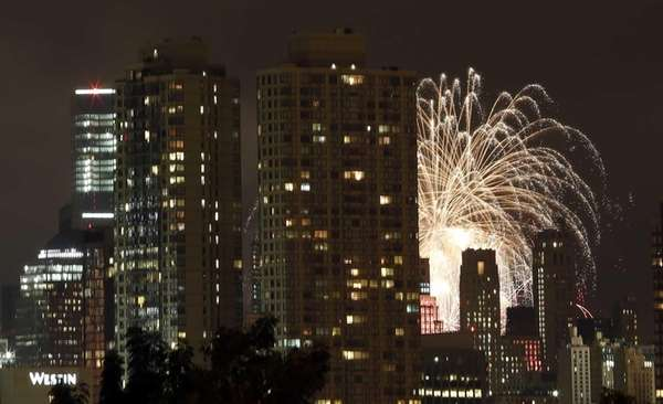 Fireworks explode over the East River behind buildings,