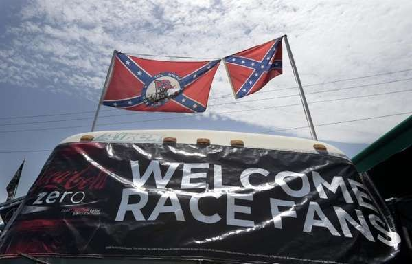 Confederate flags fly on top of a motor