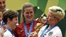 USA midfielder Megan Rapinoe (R) kiss the trophy