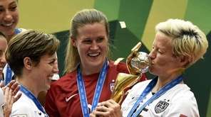 USA midfielder Megan Rapinoe kisses the trophy next