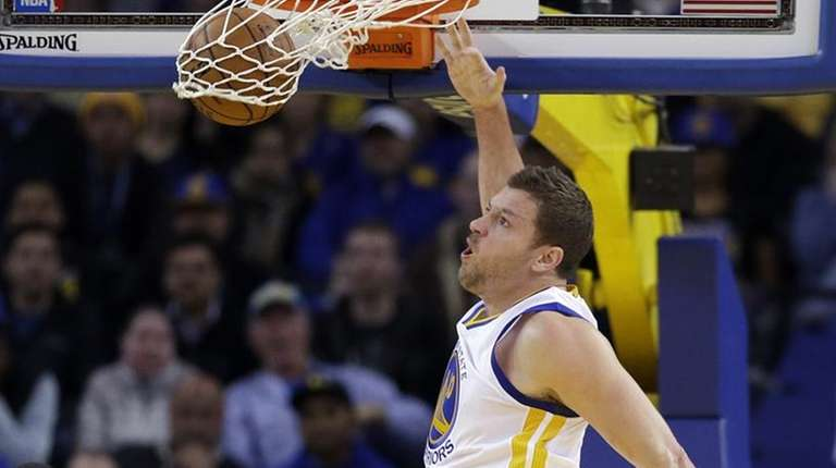 The Golden State Warriors' David Lee, right, dunks