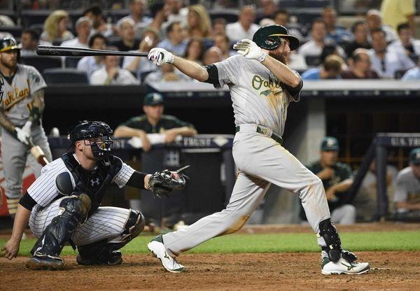 Oakland Athletics first baseman Ike Davis follows through
