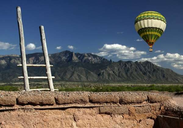 Adobe wall, balloon and the Sandia Mountains in