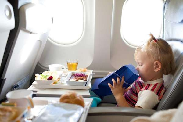 Small girl on a plane holding a barf