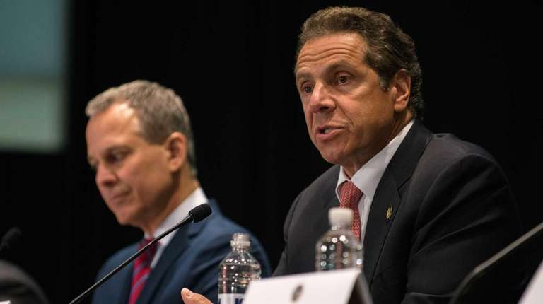 New York Gov. Andrew M. Cuomo, right, issues