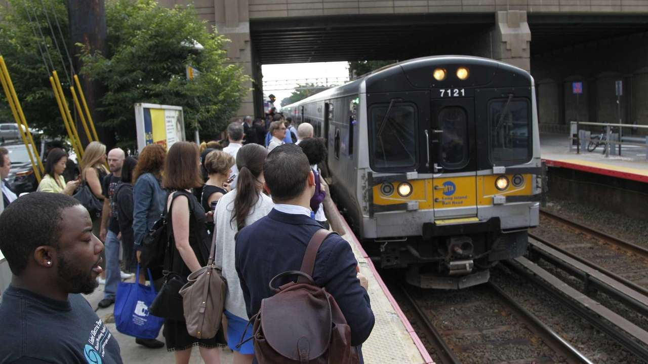 Commuters crowd the westbound platform at the Mineola