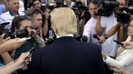 Republican presidential candidate Donald Trump is surrounded by