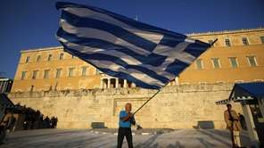 A pro-euro demonstrator waves a Greek flag in