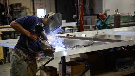 A worker welds the frame of a sign