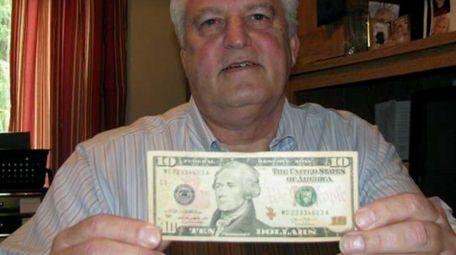 Doug Hamilton holds a $10 bill bearing the