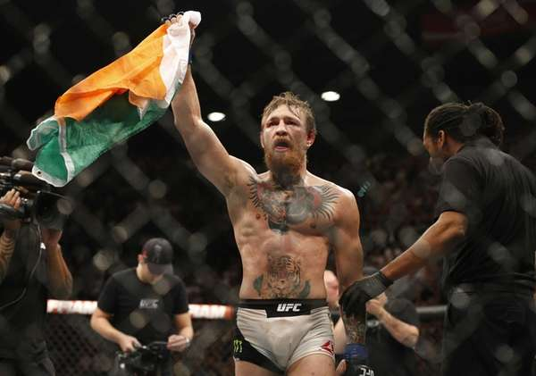 Conor McGregor celebrates after defeating Chad Mendes during