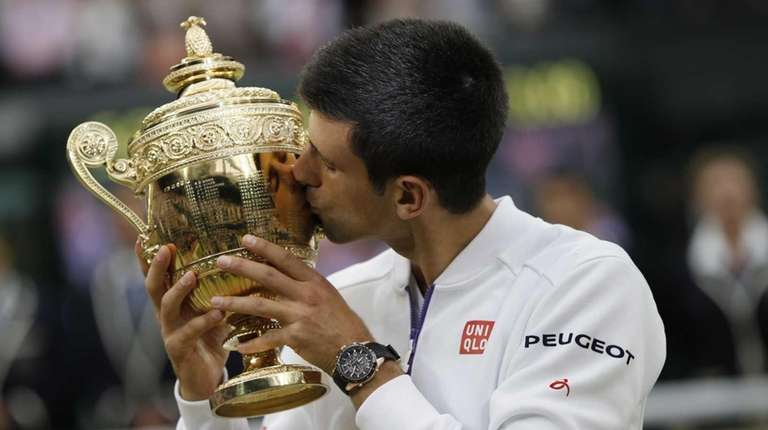 Novak Djokovic kisses the winner's trophy after beating