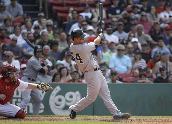 The New York Yankees' Rob Refsnyder, right, hits