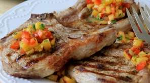 Seasoned grilled pork chops are topped with fresh