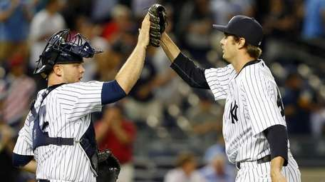 Andrew Miller #48 and Brian McCann #34 of