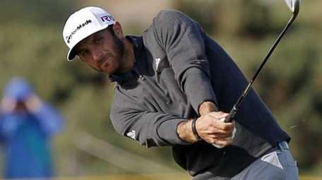 Dustin Johnson plays from the rough during the