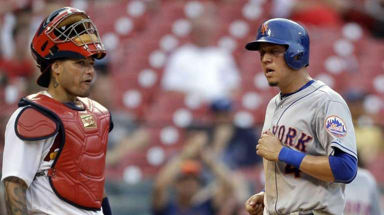 The Mets' Wilmer Flores, right, scores past St.