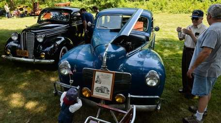 People look at rows of vintage cars during