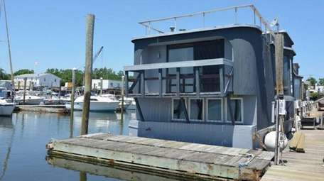 A floating houseboat complete with a rooftop deck