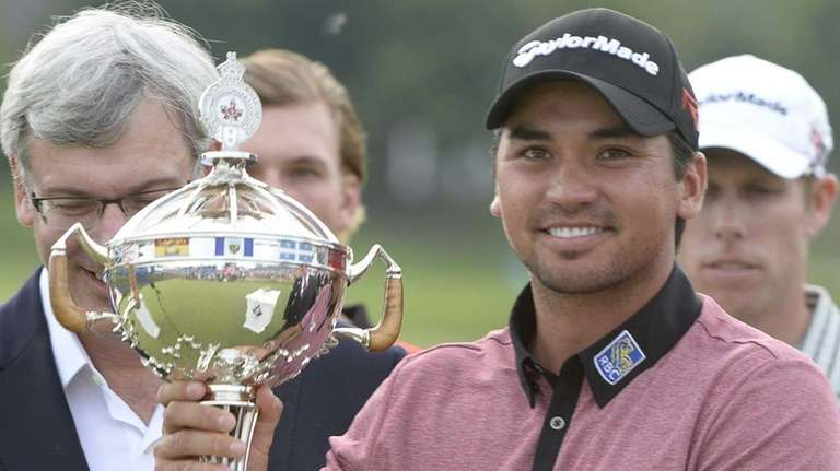 Jason Day holds the winner's trophy at the