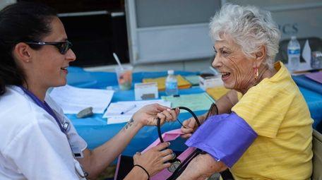 Winthrop Nurse Christine Pagano, left, takes Hewlett resident