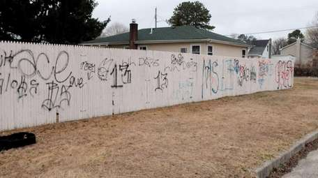 MS-13 gang and other graffiti is painted a
