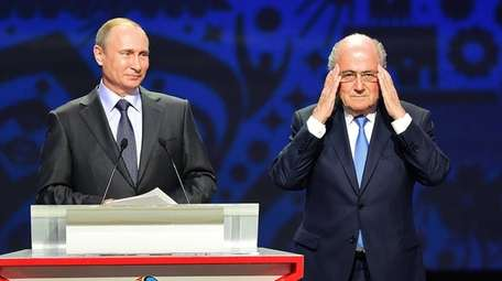 Vladimir Putin and FIFA President Sepp Blatter speak