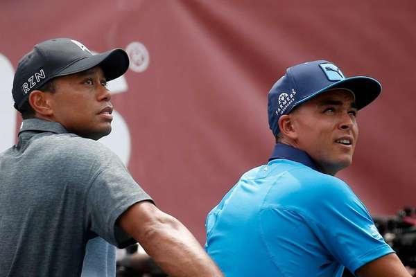 Ricky Fowler, right, and Tiger Woods look on