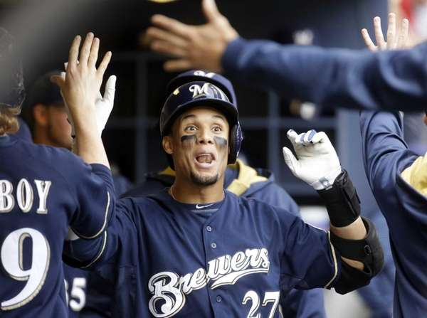 The Milwaukee Brewers' Carlos Gomez is congratulated in