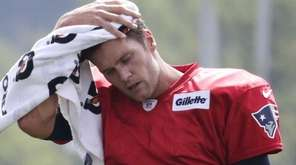 New England Patriots quarterback Tom Brady wipes the